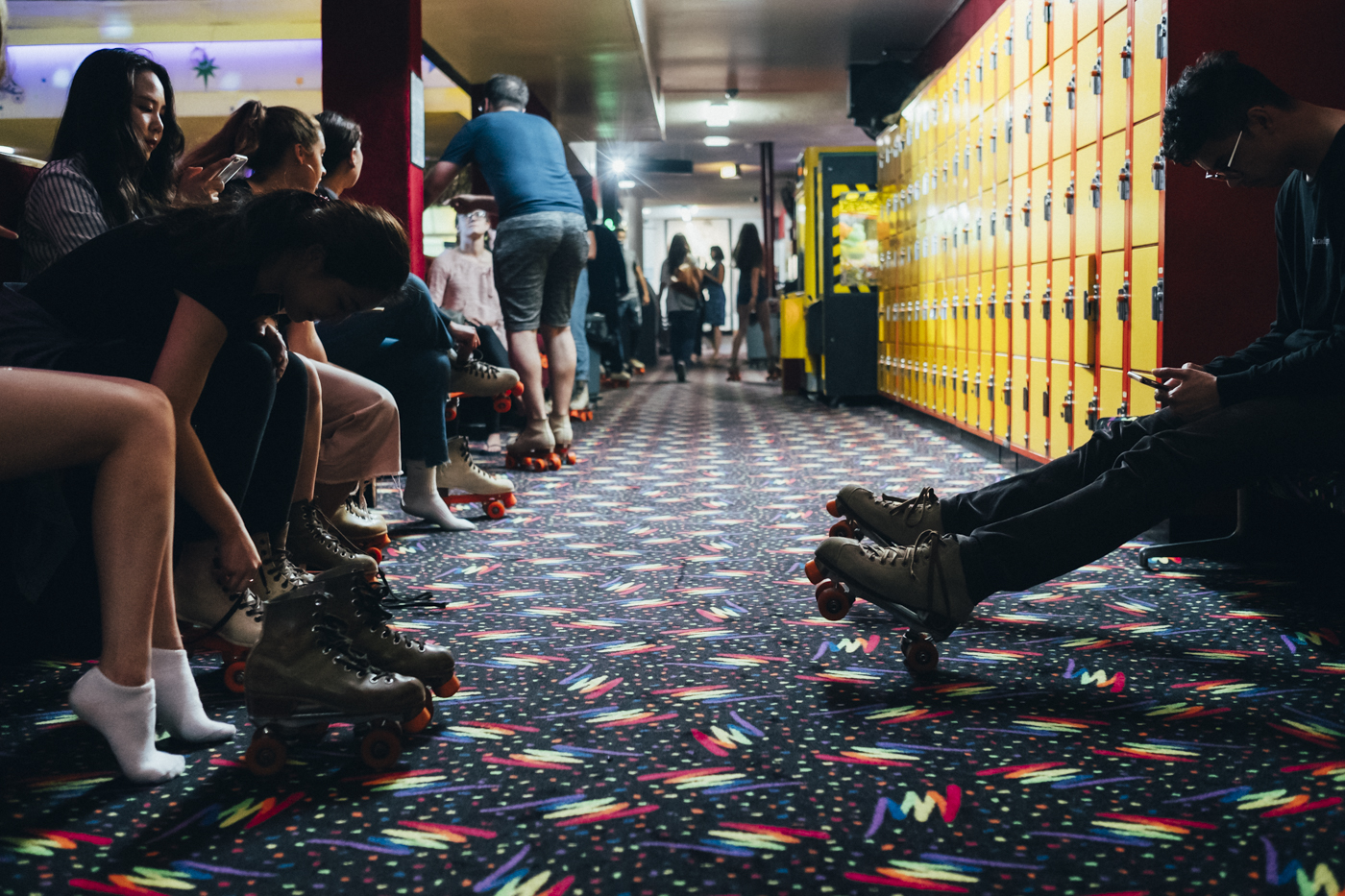 All around the rink, alleys with carpets as in the 70s. Young people rest there, beginners recover from their emotions before  nding the courage to return to the rink, and most of them  irt and have fun